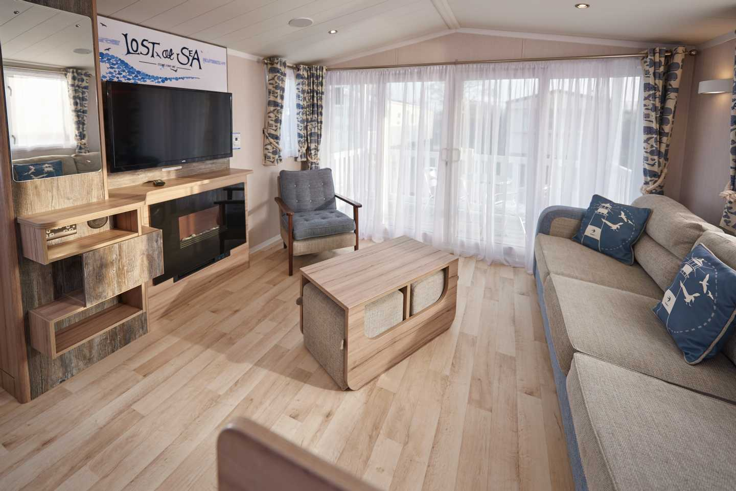 A Platinum with Decking caravan lounge with sofa, TV, fireplace and table