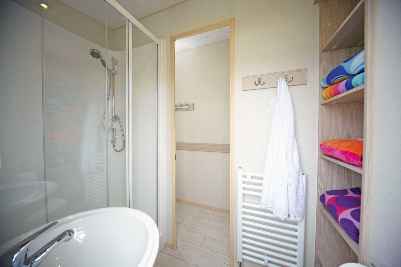 A Prestige caravan bathroom with shower, sink and storage