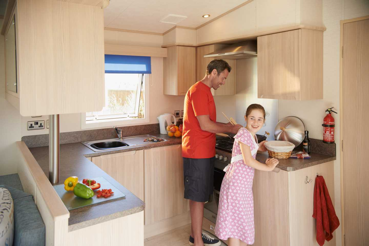 A father and daughter in a Prestige caravan kitchen making dinner