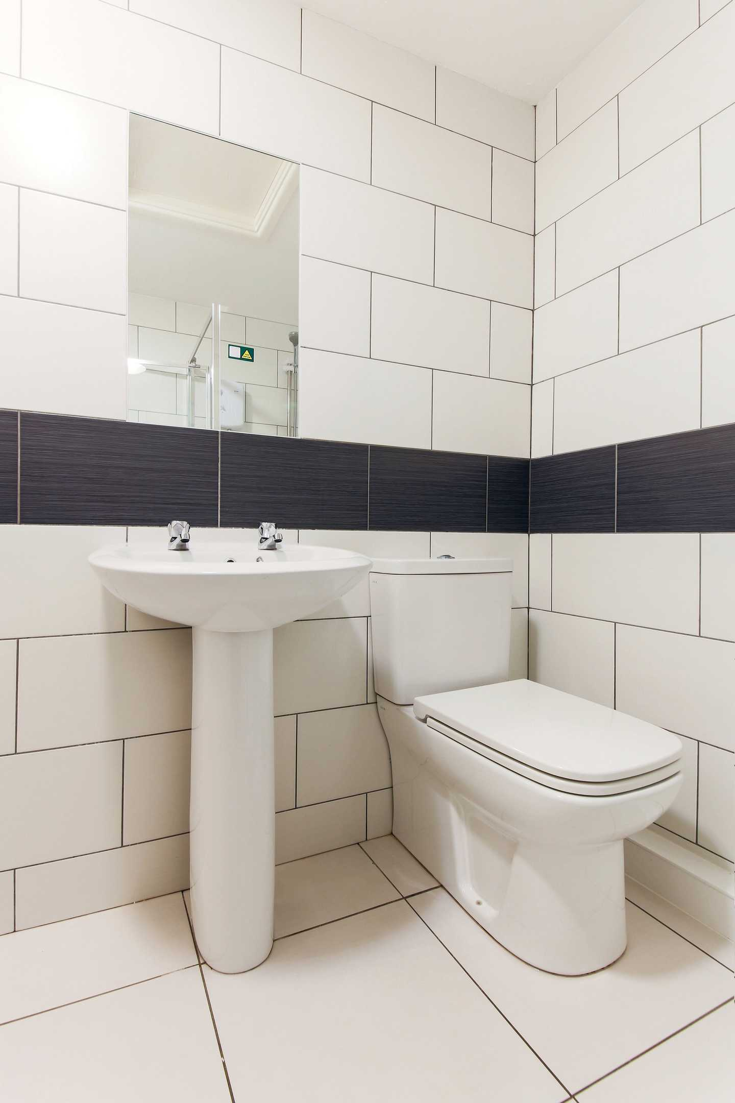 A Premier chalet bathroom with toilets, sink and mirror