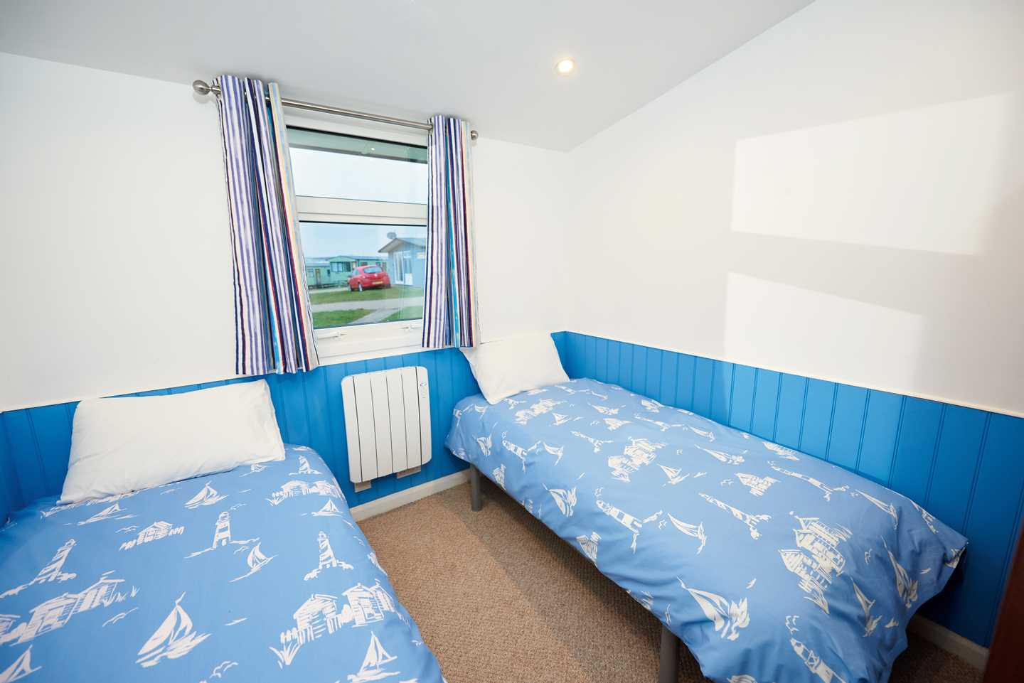 A Comfort chalet twin bedroom with two beds and a radiator