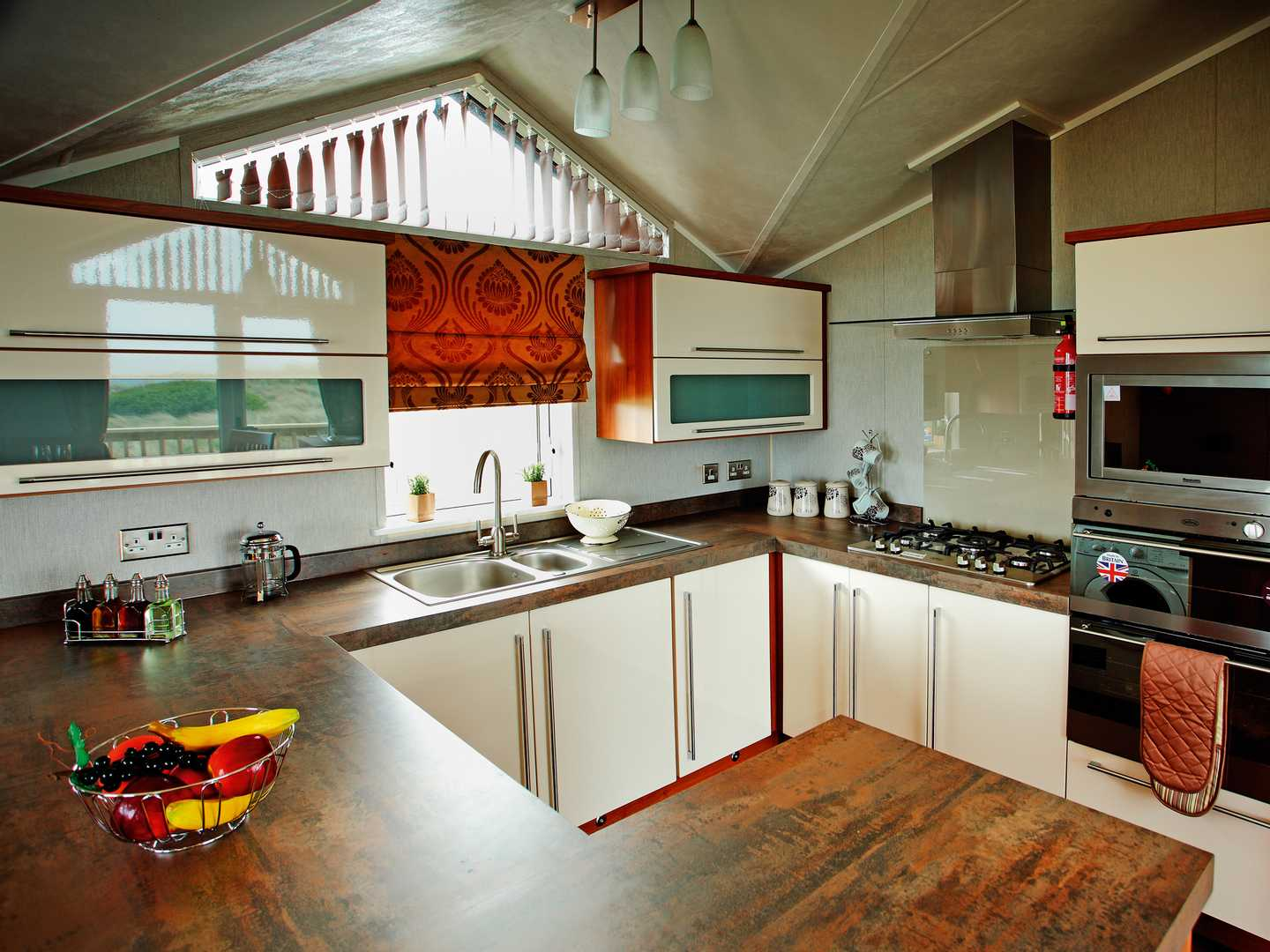 A Luxury Lodge kitchen with oven, sink, gas hobs, storage cupboards