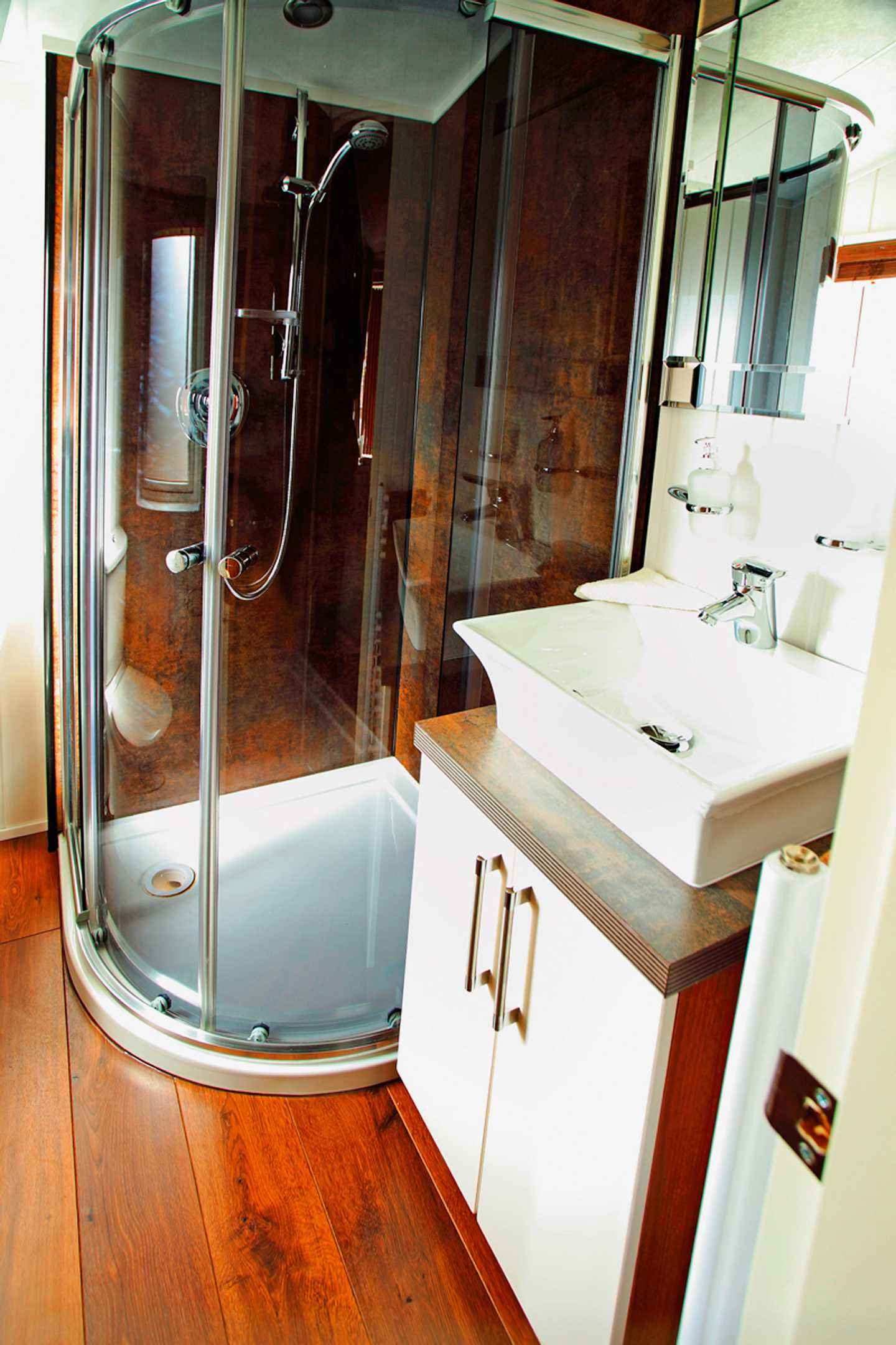 A Luxury Lodge bathroom with walk-in shower, sink and storage cupboard