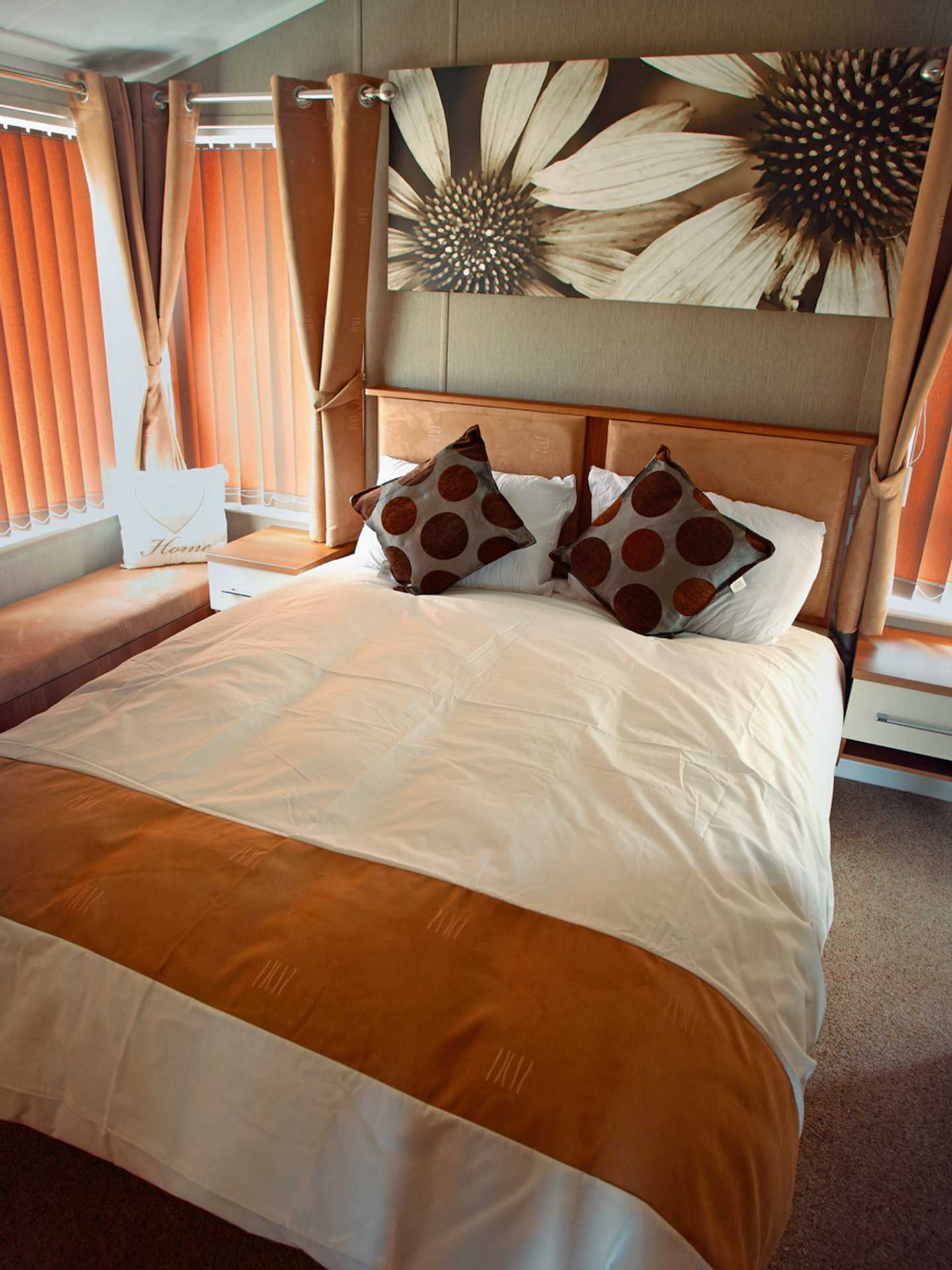 A Luxury Lodge master bedroom with double bed, canvas picture above the bed and side tables