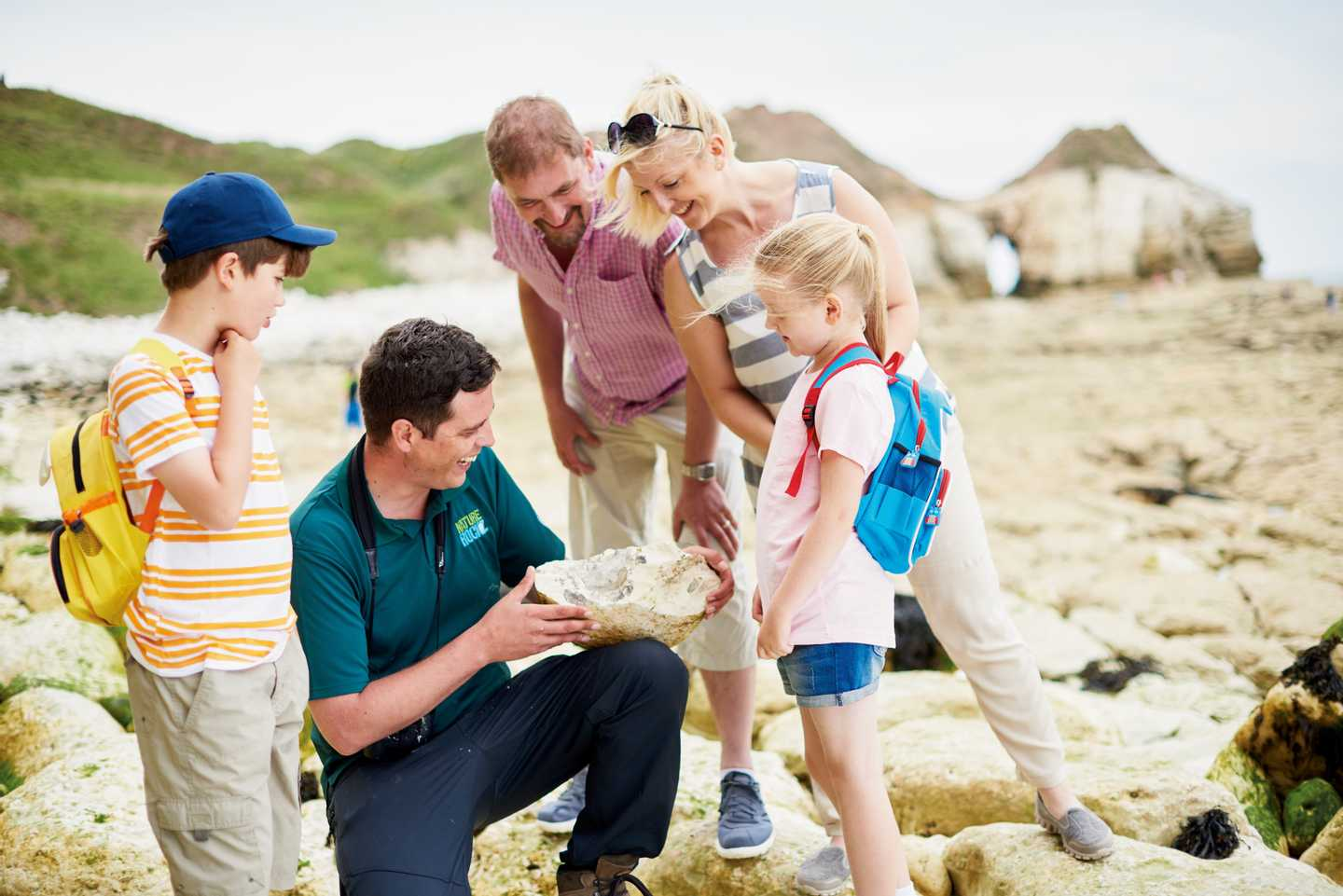 Family gathered around instructor at the beach