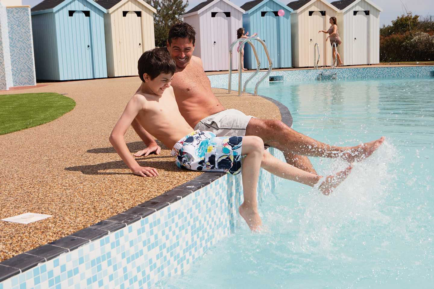 Father and son kicking their feet in the heated outdoor pool