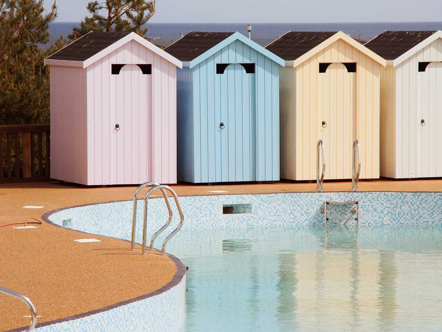 Four pastel coloured beach hut changing rooms standing by the outdoor pool on a bright, sunny day
