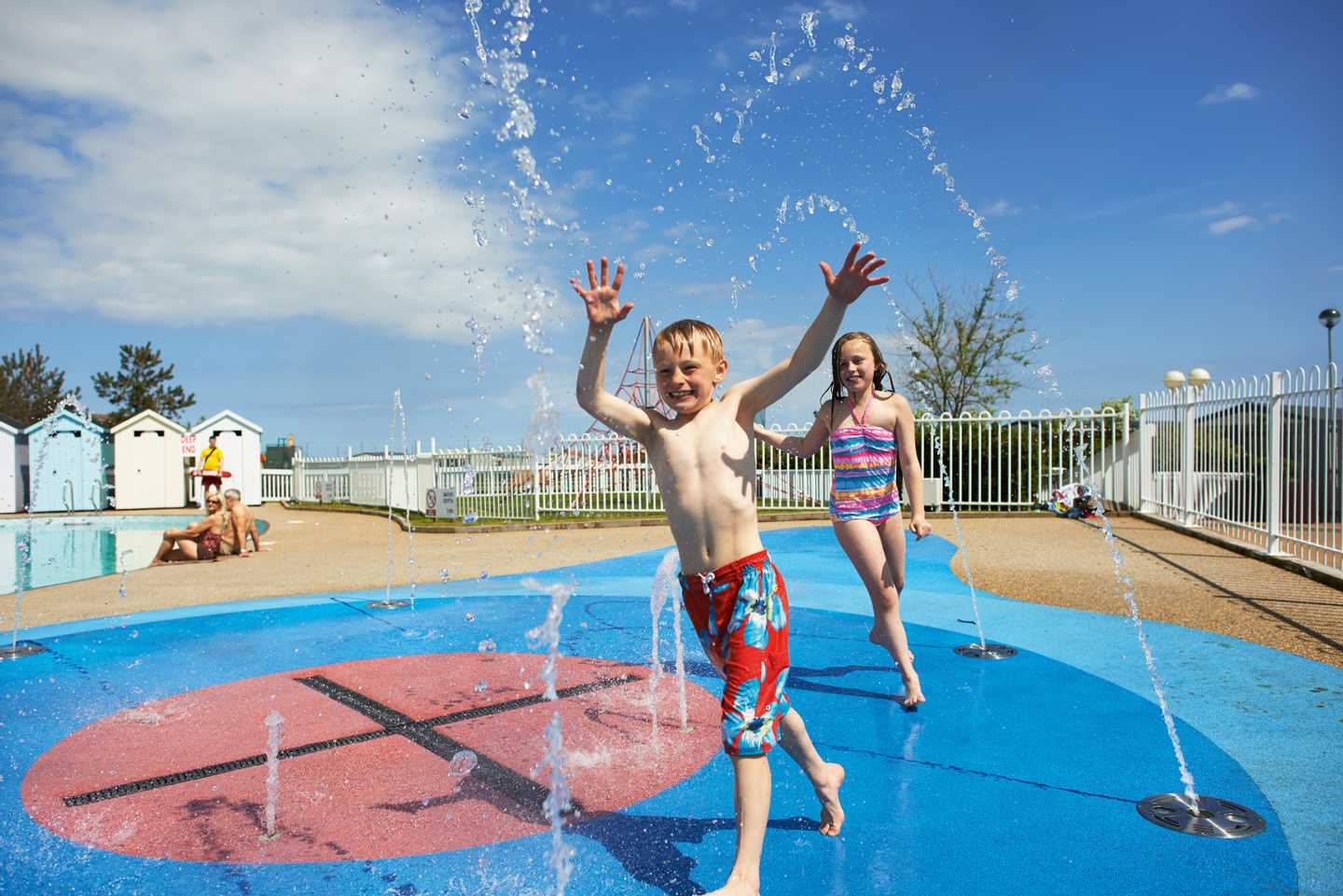 A brother and sister playing on our outdoor SplashZone