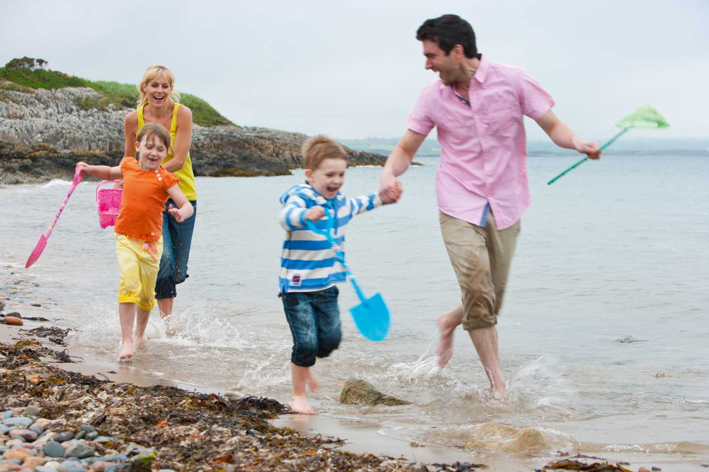 A family playing on the beach near Hafan y Môr