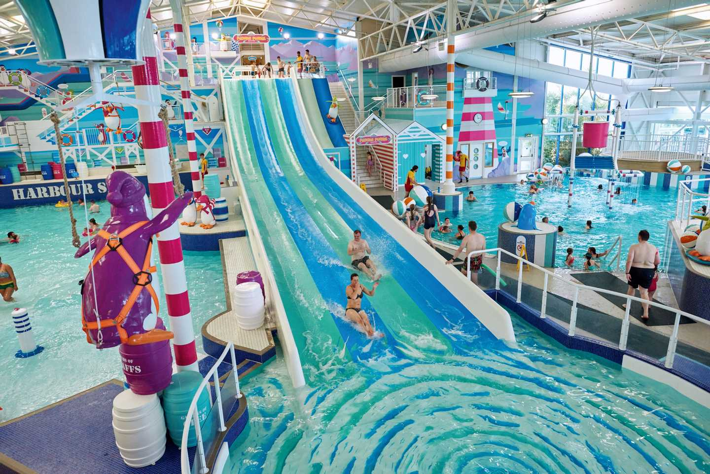 Families sliding down the 4-lane water slide in the heated indoor pool at Hafan y Môr