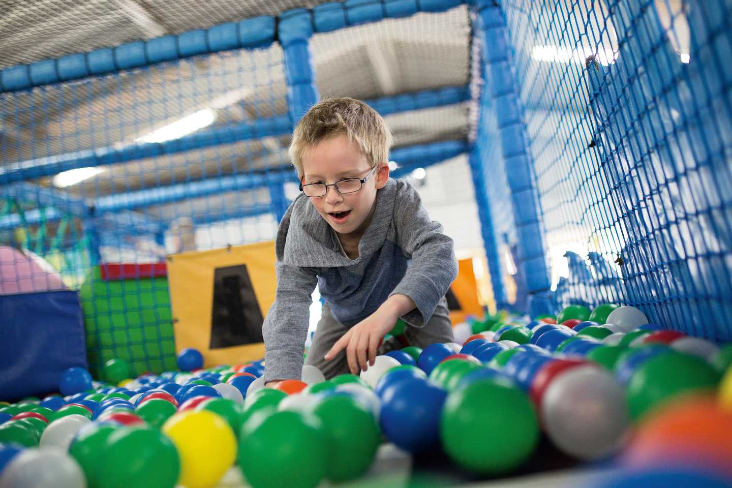 A child playing in the ball pit in the soft play area