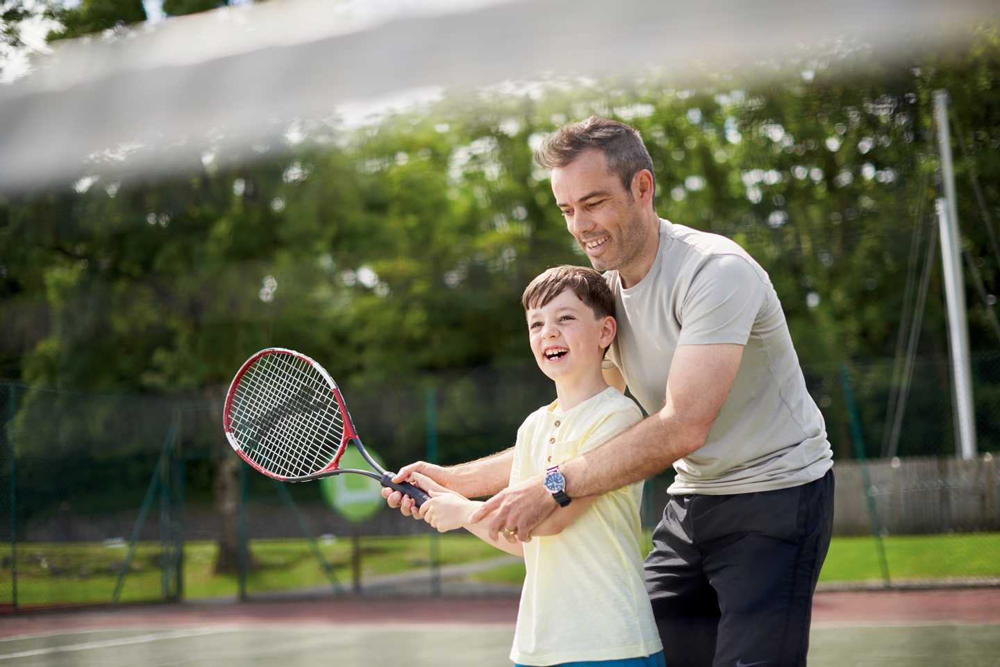 A father helping his son play tennis