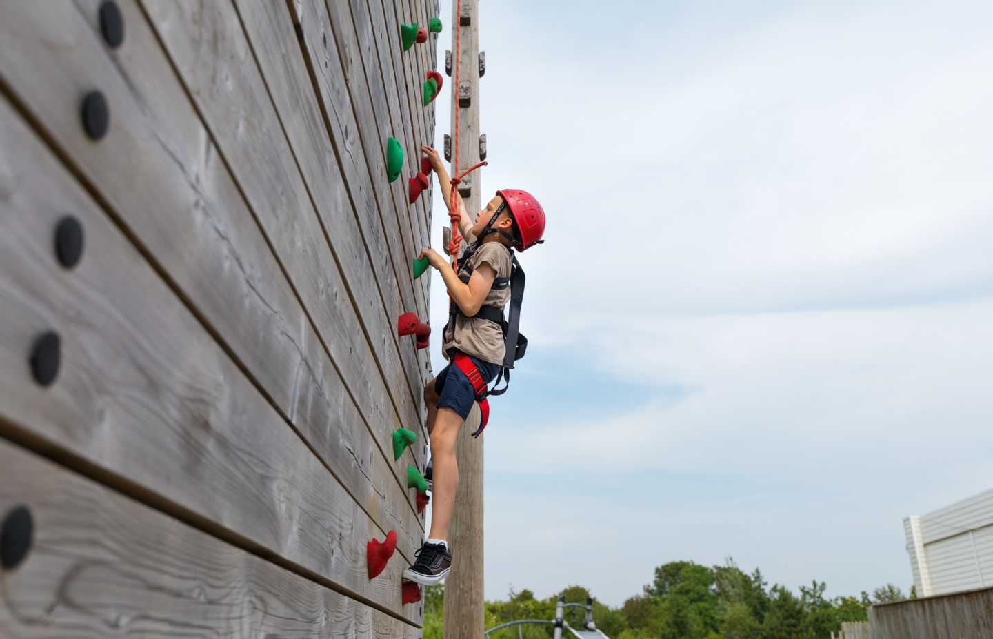 Child climbing on the outdoor climbing wall