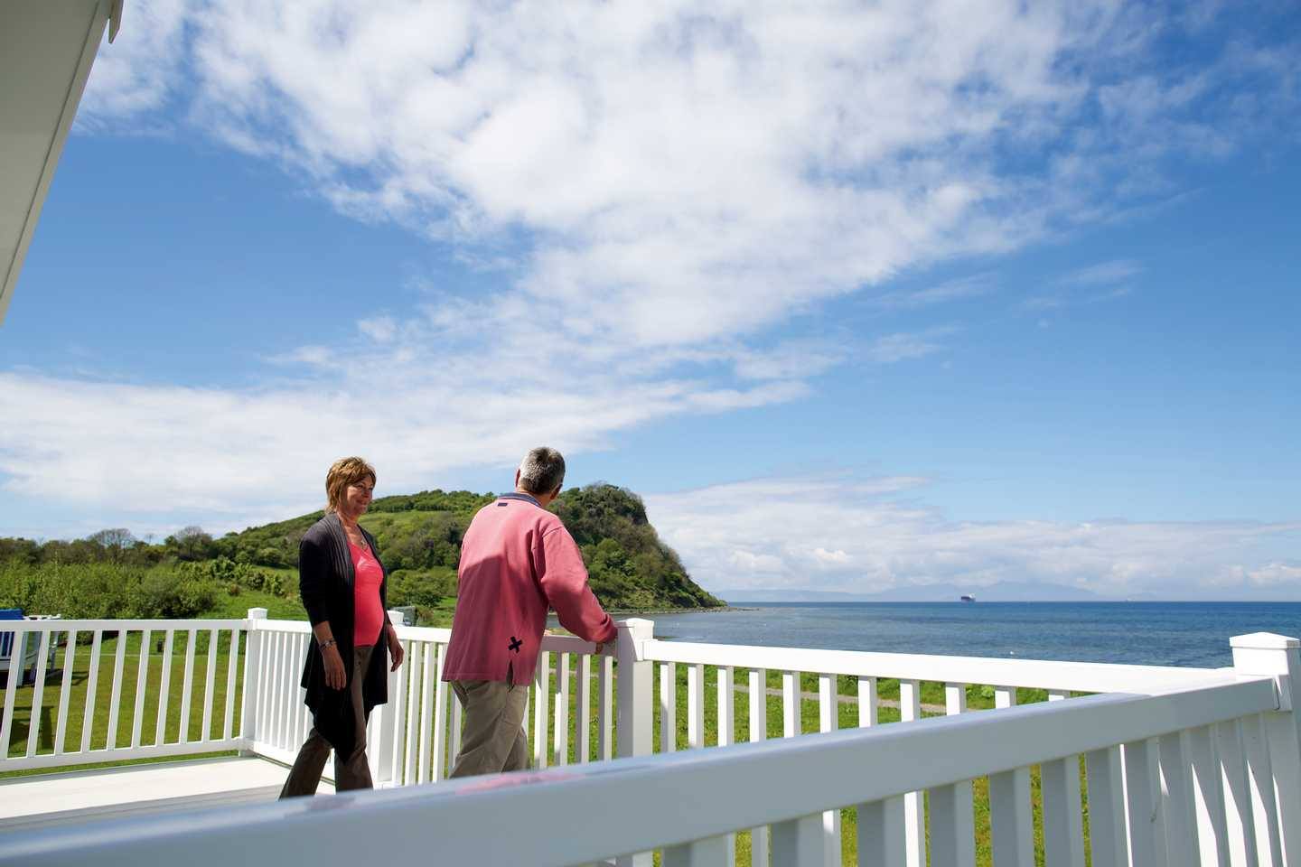 A couple enjoying a sea view from their holiday homes veranda with wide, open skies and mountains in the distance