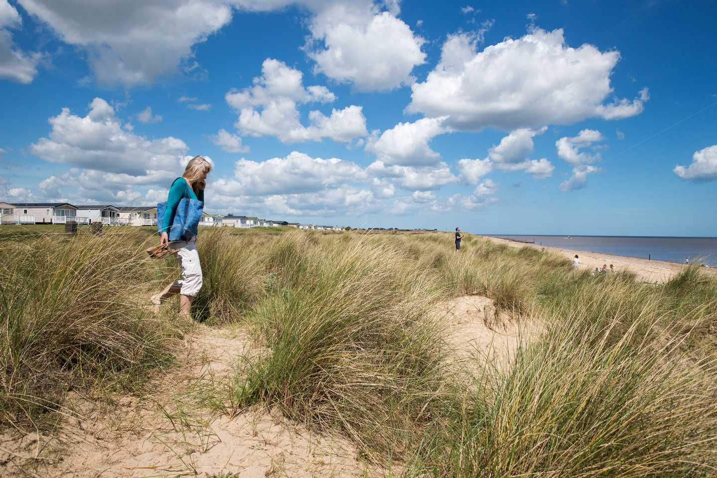 A lady holding her shoes as she walks across sand dunes towards the main beach and sea on a blue, sunny day with some white fluffy clouds in the sky