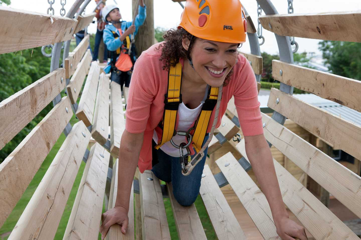 A woman smiling in safety gear crawling through an Aerial Adventure course that is suspended in the air at Devon Cliffs Holiday Park