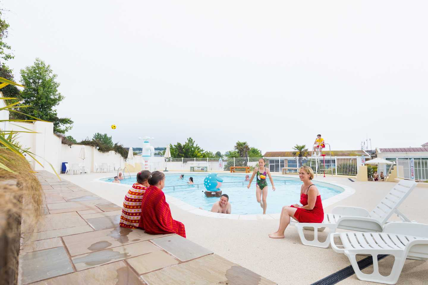 Families enjoying the outdoor pool at Devon Cliffs Holiday Park