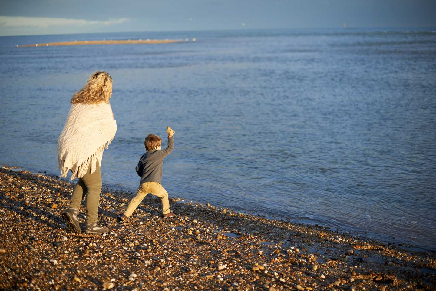 A mother waiting while child runs to sea