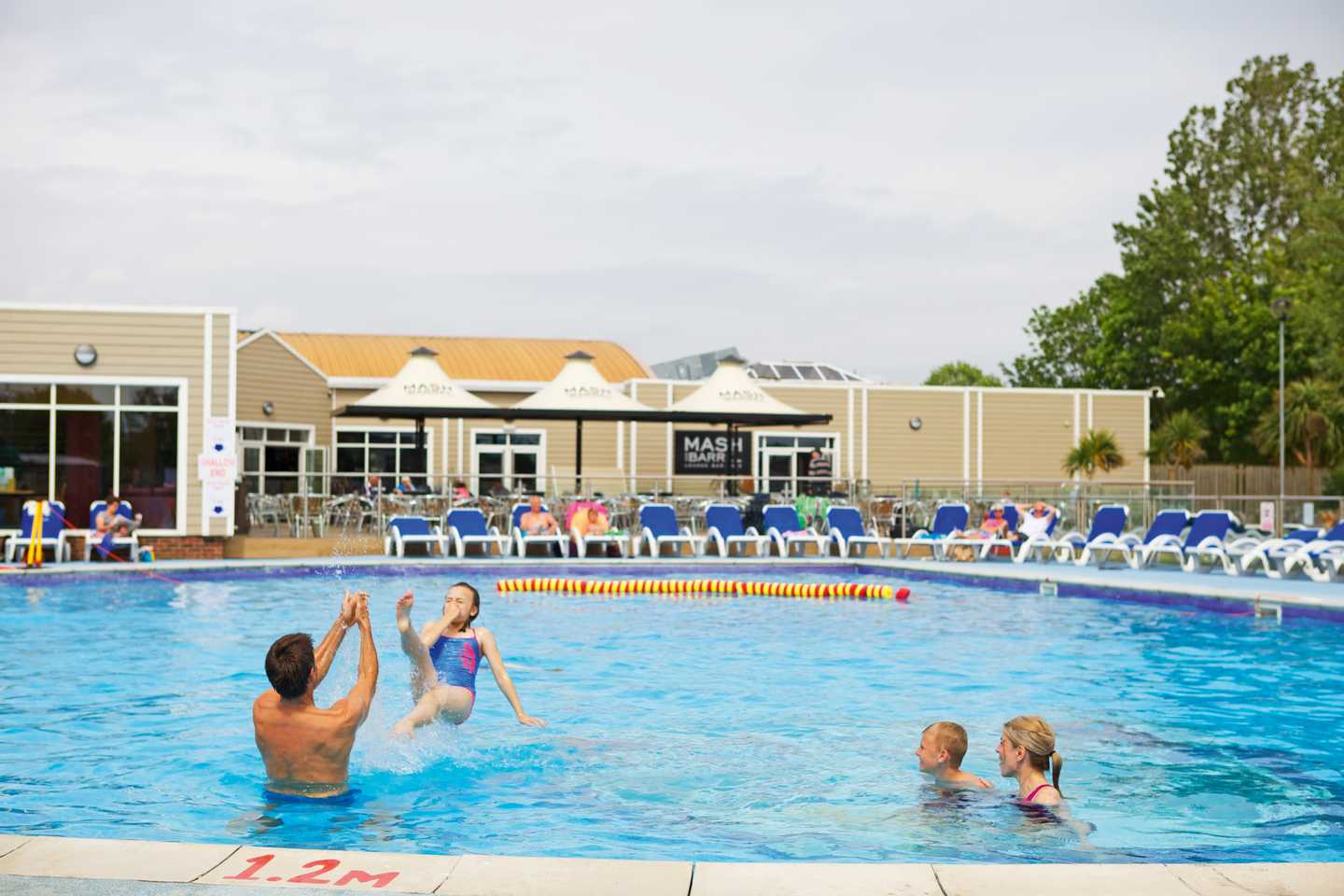 Family splashing around in the heated outdoor pool