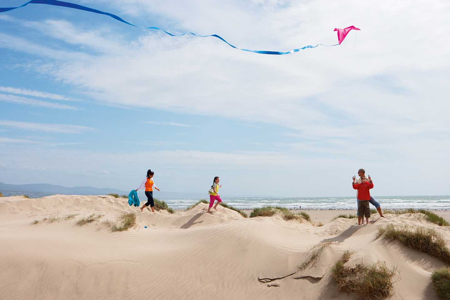 Family on the dunes flying a kite