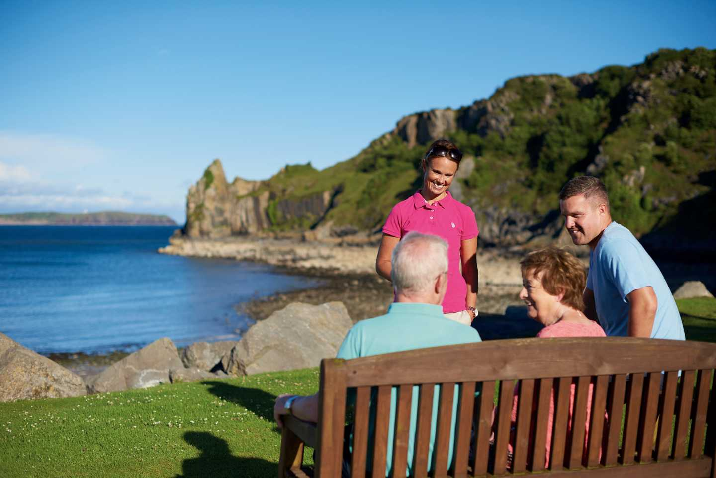 Guests sitting on a bench looking out to sea