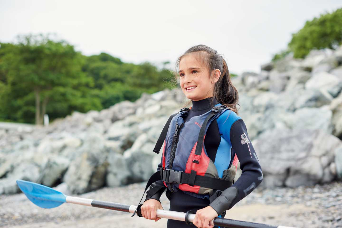 Girl standing with oar ready to kayak
