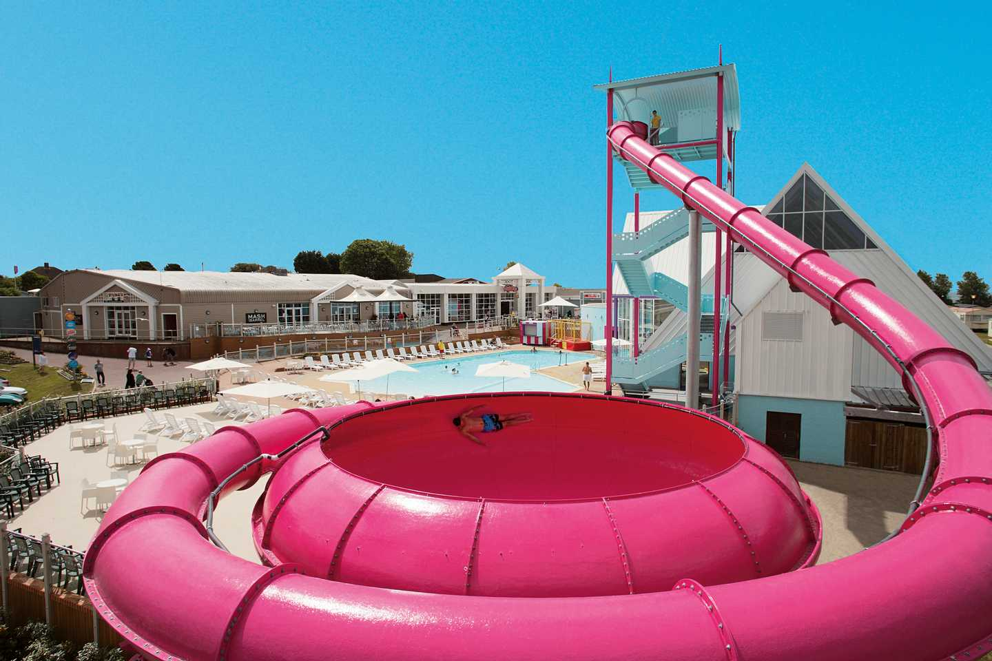 An aerial view of a man sliding through the pink Space Bowl flume