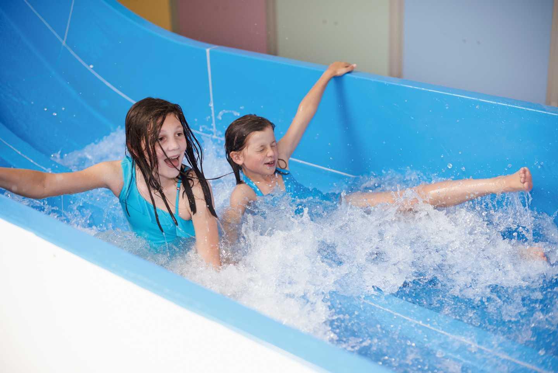 Children sliding down the indoor pool