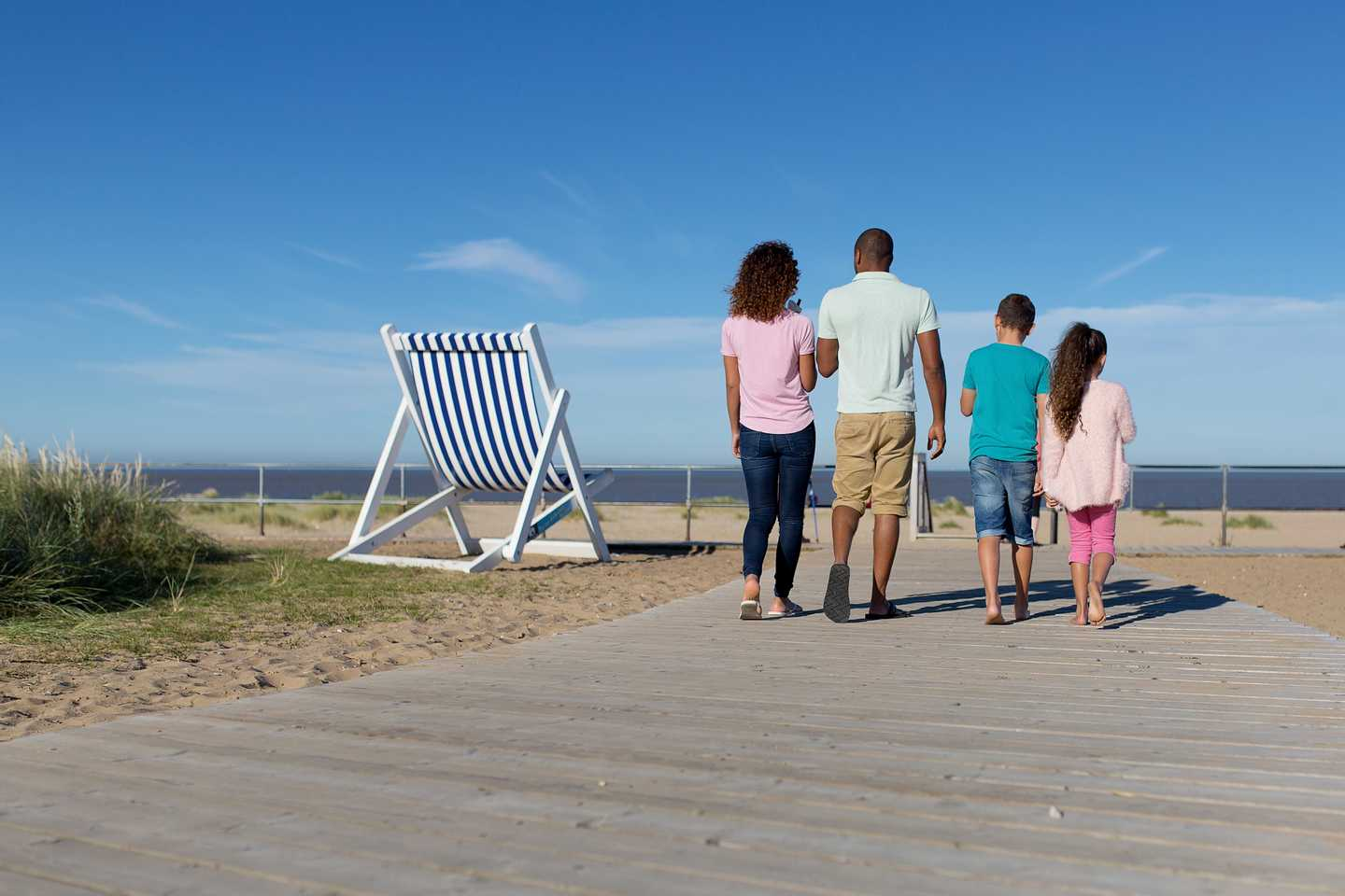 A family taking a stroll towards the beach at Caister-on-Sea with an extra large deckchair in the background