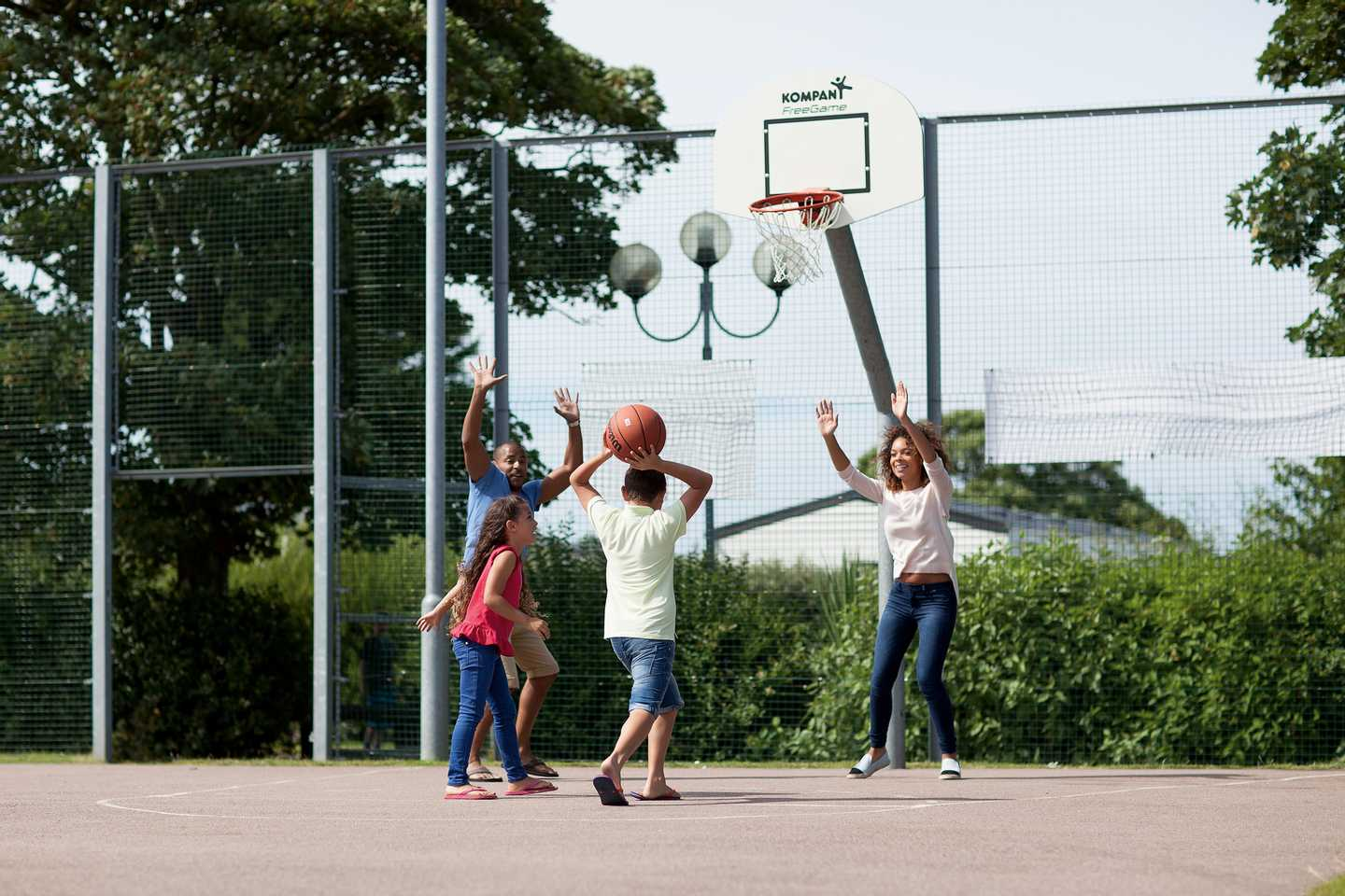 A family playing basketball in the sports court