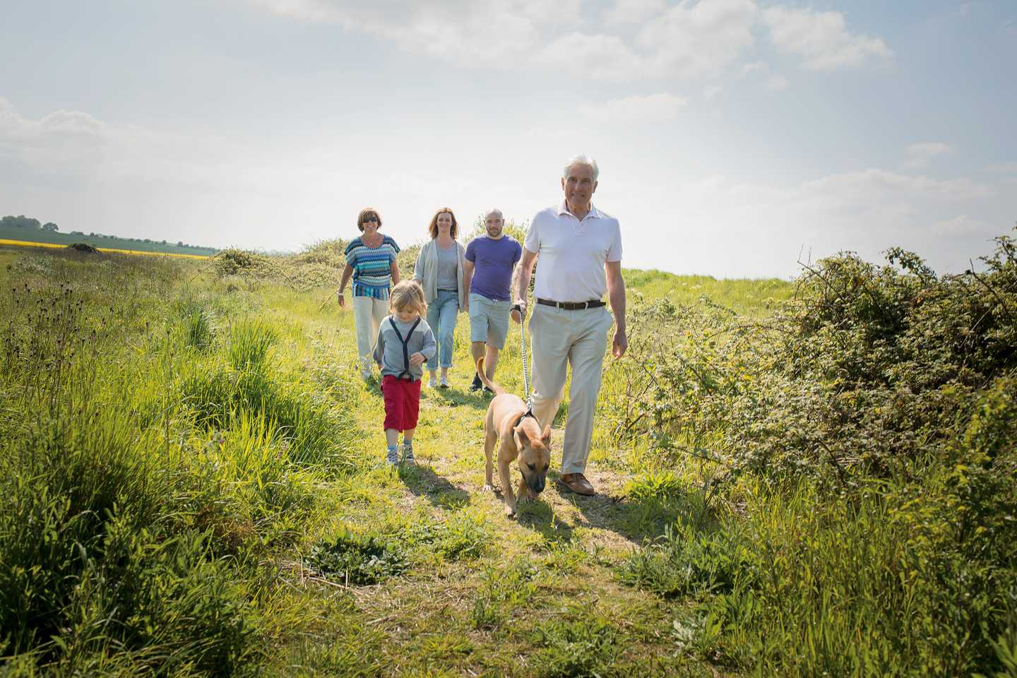 A family walking through the nature reserve on the park with their dog