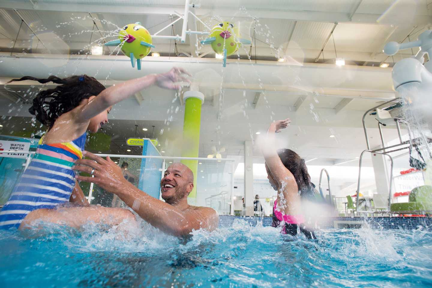 A family splashing around in the heated indoor pool