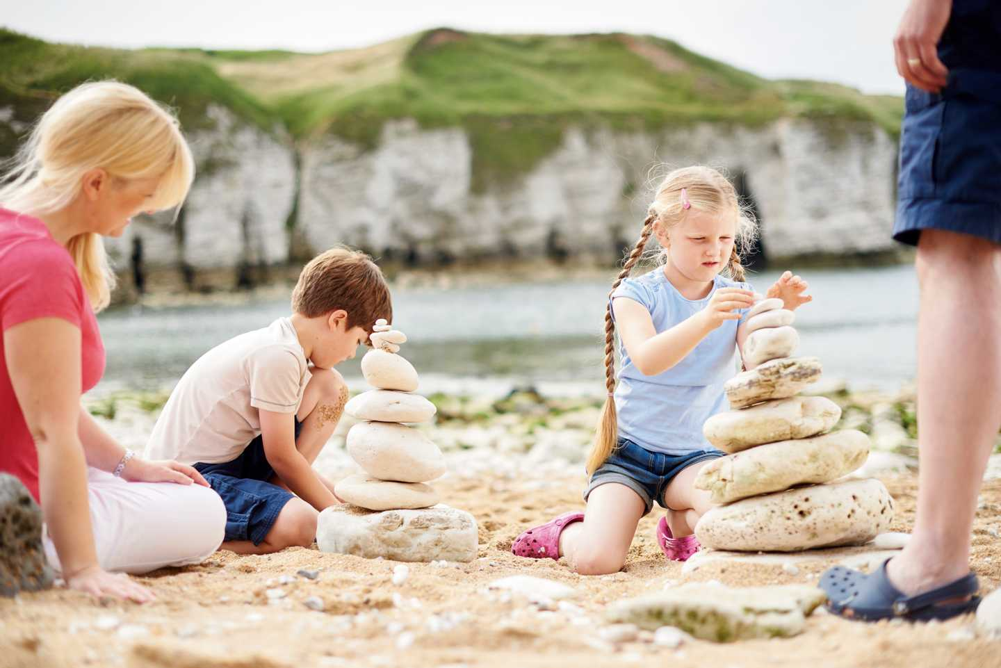 A family building mounds with white, round stones on the beach together with the sea and white cliffs in the background