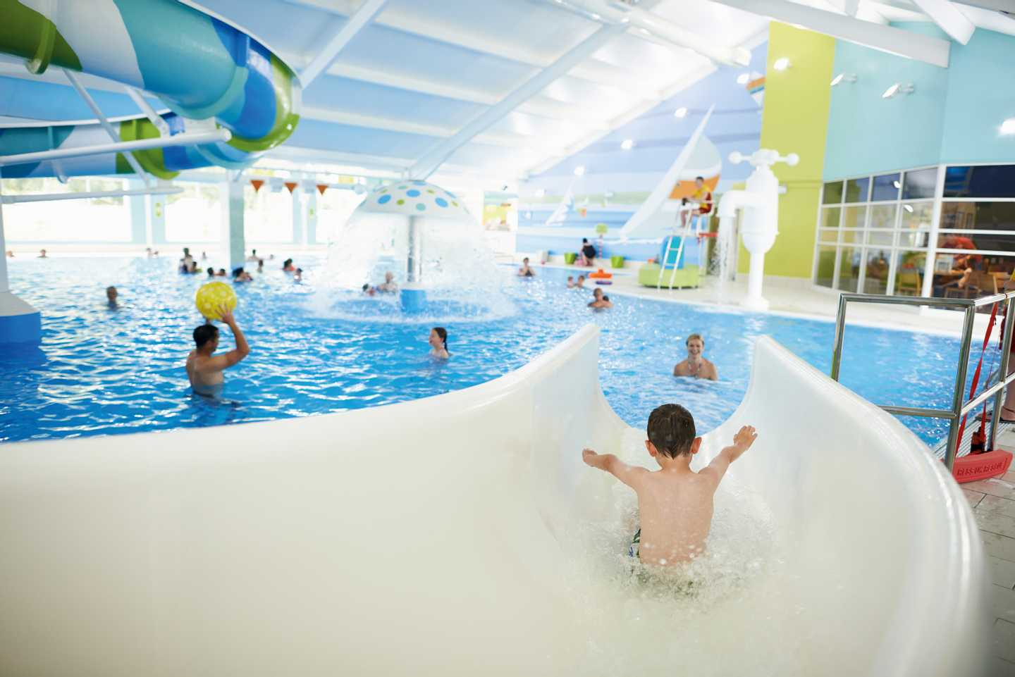 A guest sliding down the indoor pool slide
