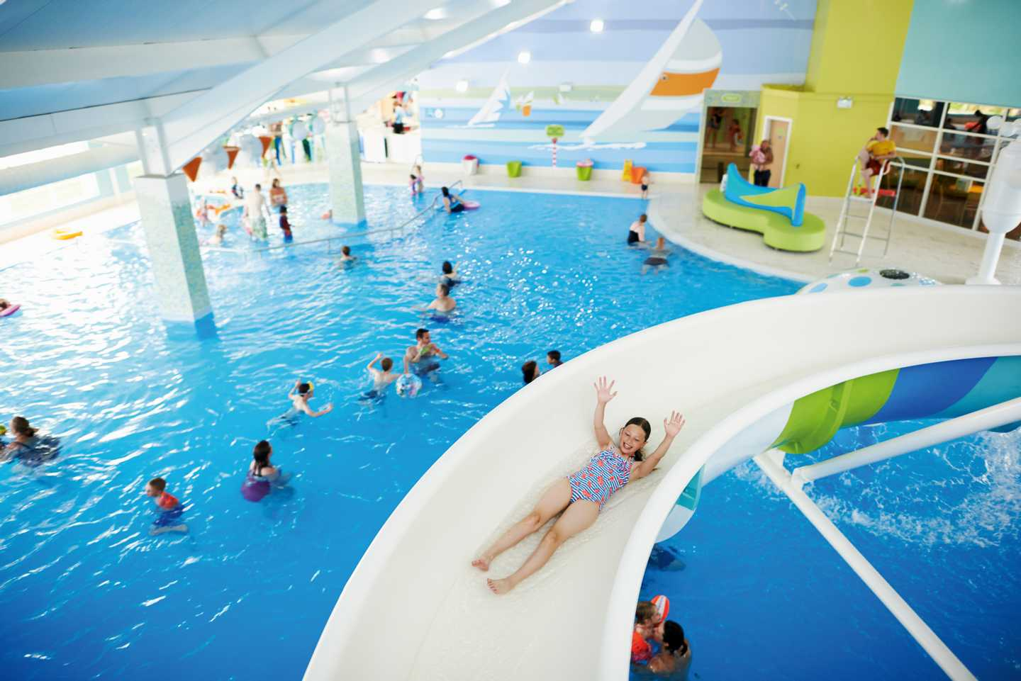 A girl sliding down a water slide in the heated indoor pool