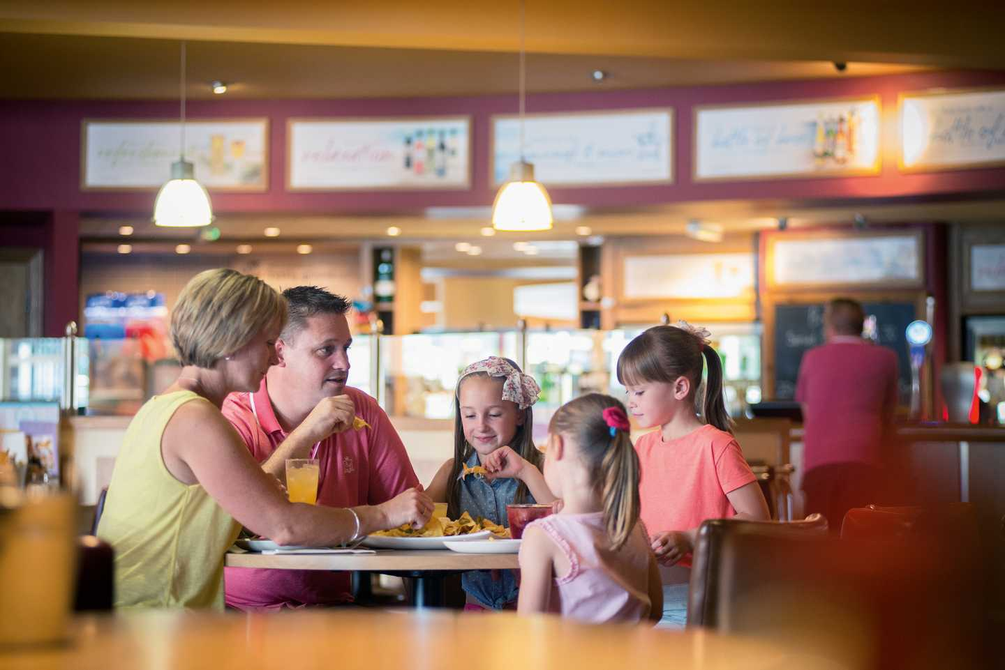 A family enjoying food and a drink in the Mash and Barrel restaurant at Burnham-on-Sea