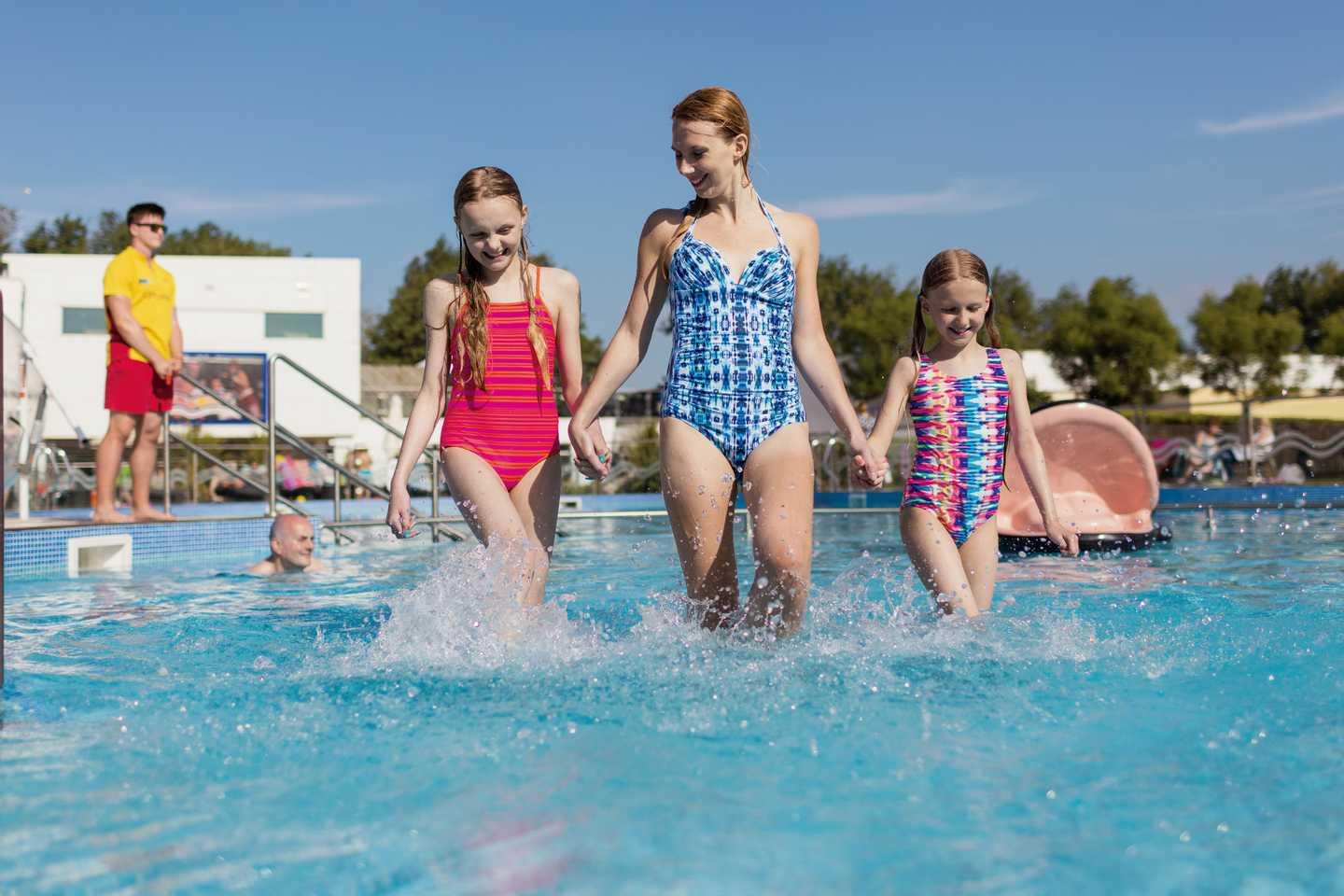 A family walking through the outdoor pool