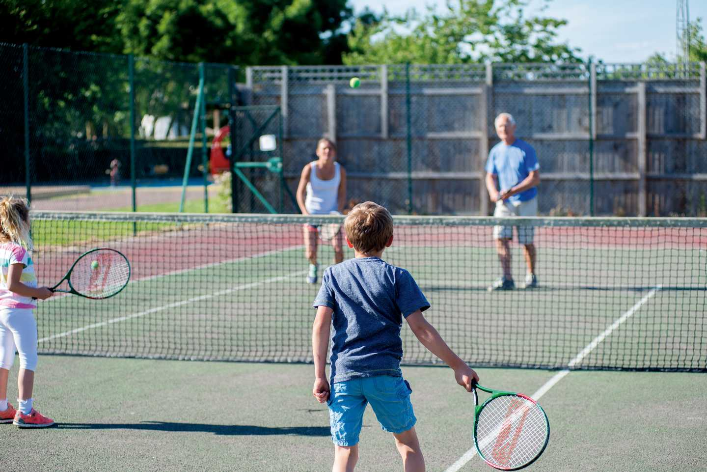 Family playing tennis on out tennis courts