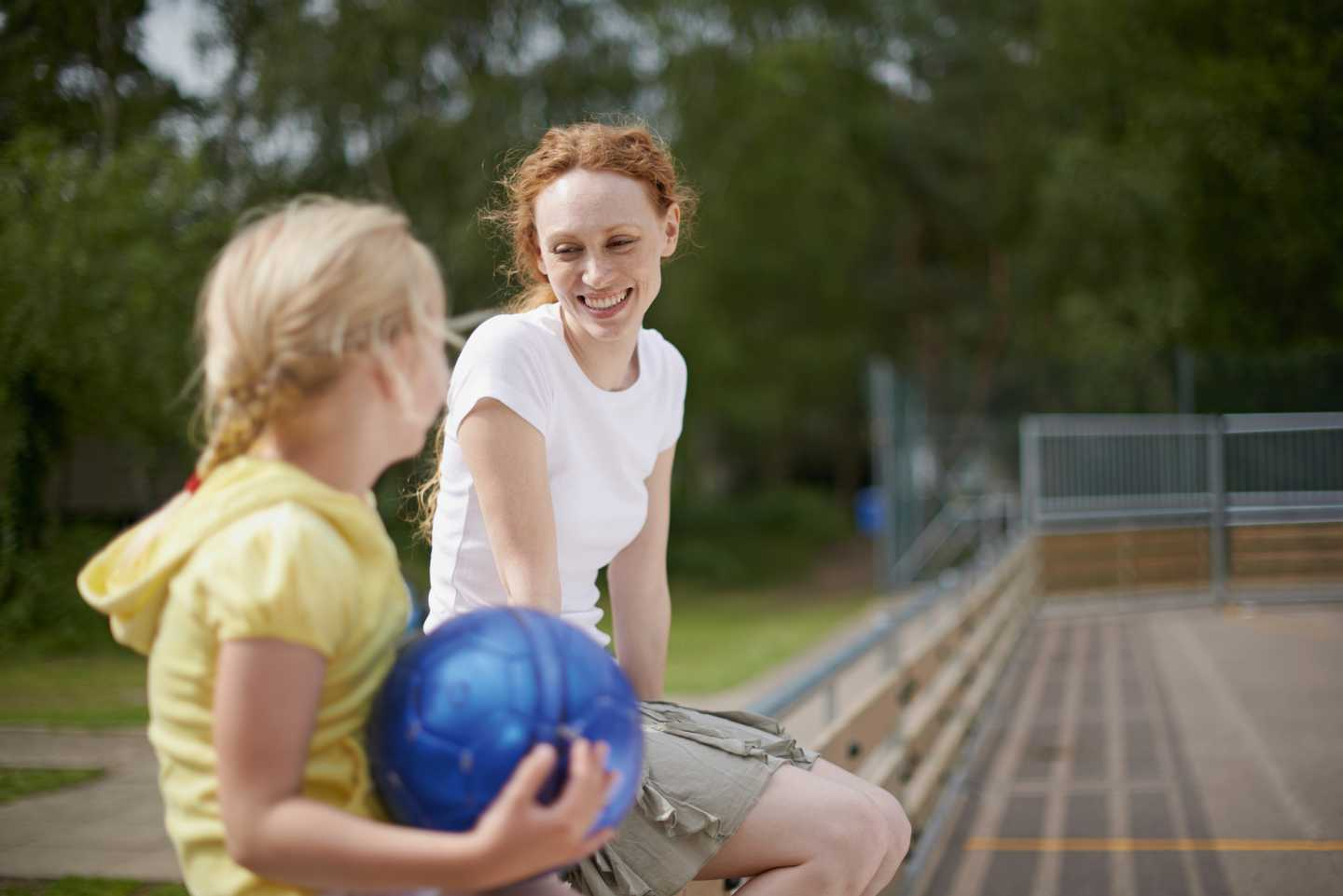 Two girls sitting in the sports court