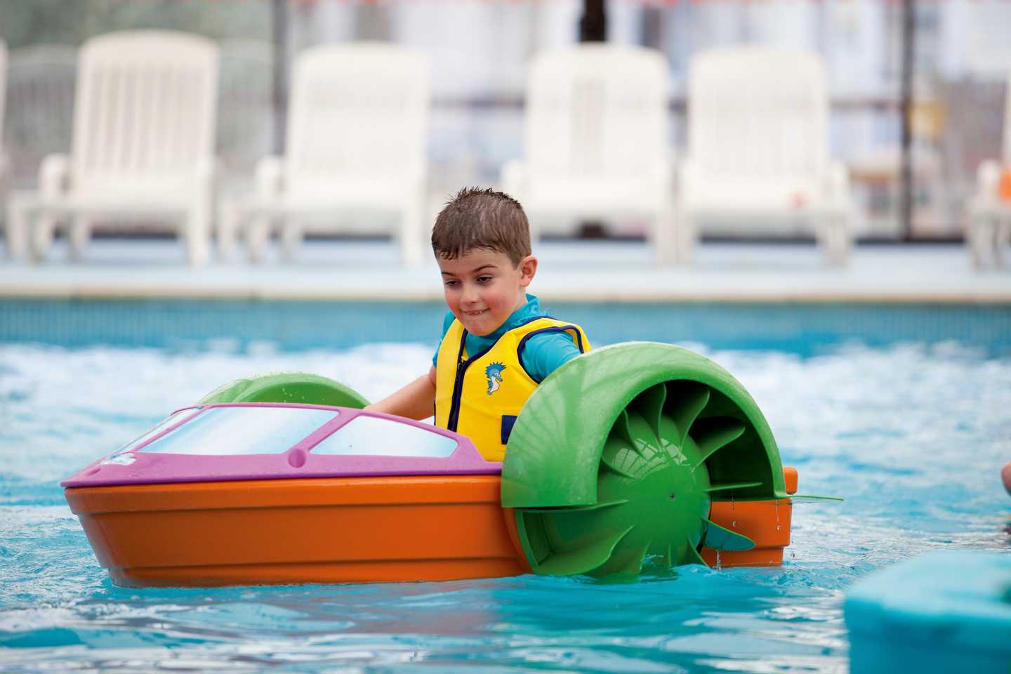 Boy playing in pool on Aqua Paddler
