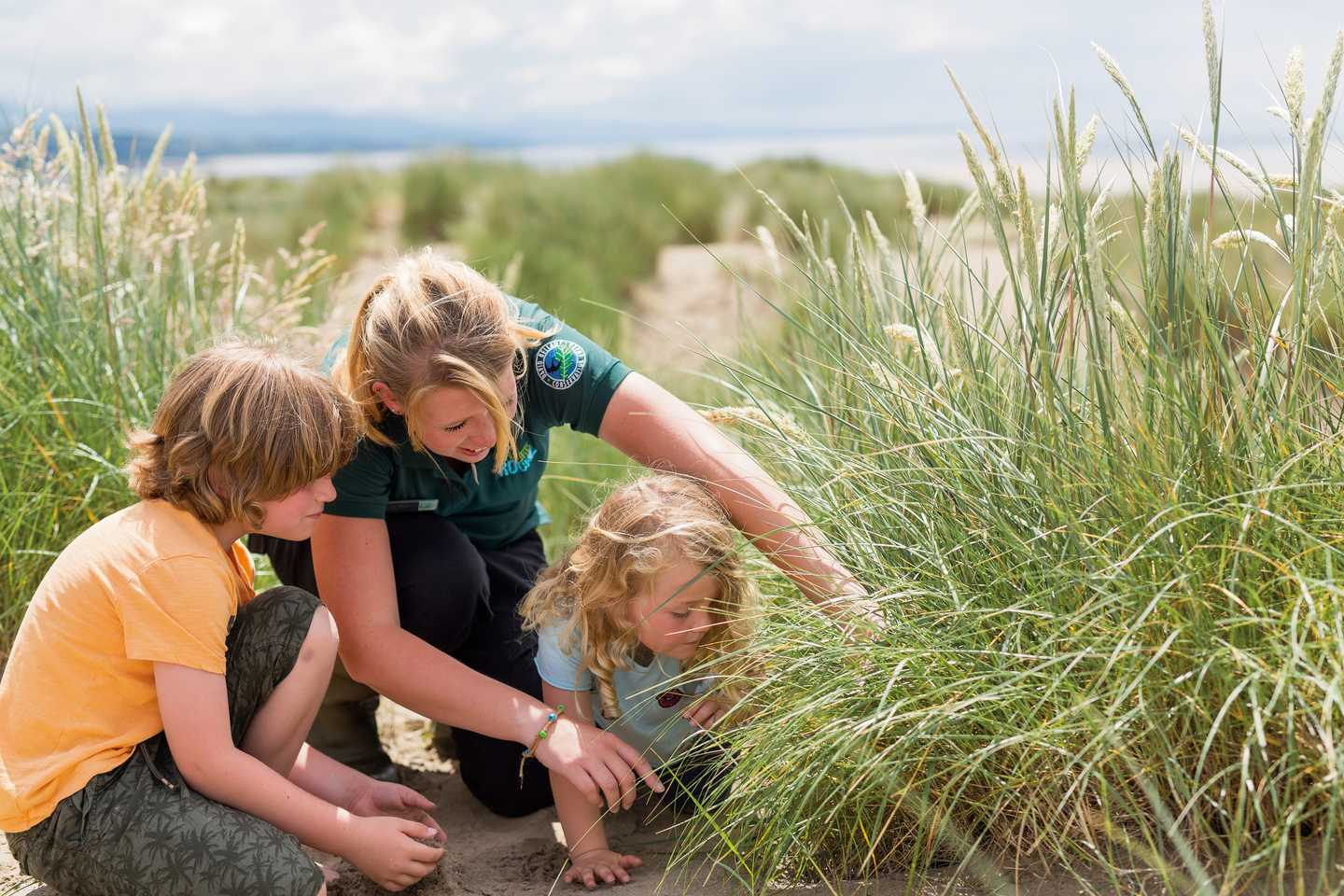 Family and Nature Rockz ranger examining wild grass in dunes