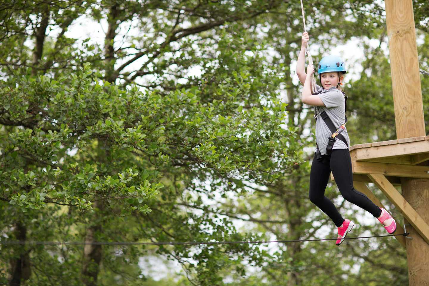 Girl swinging on the aerial adventure course