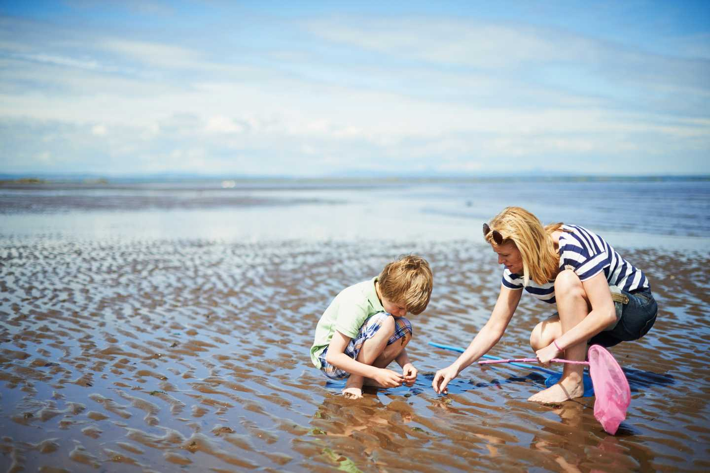 A mother and son on the beach playing in the shallow water of the sea