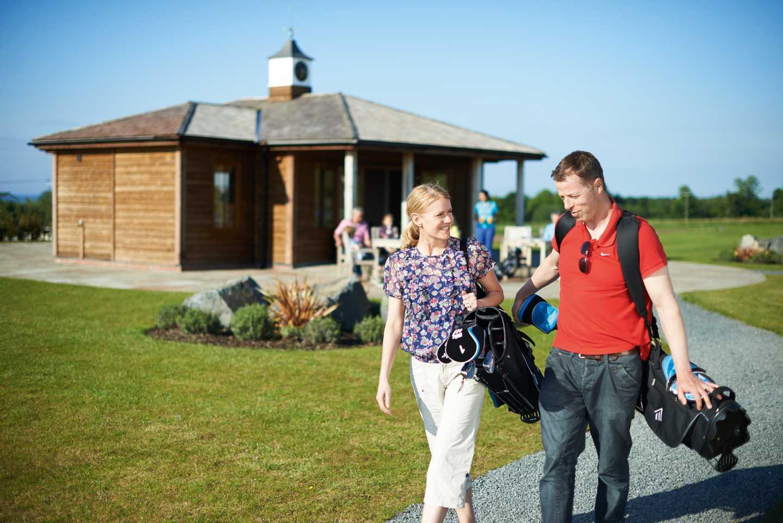 A couple walking along the 9-hole par 3 golf course wearing a golf bag