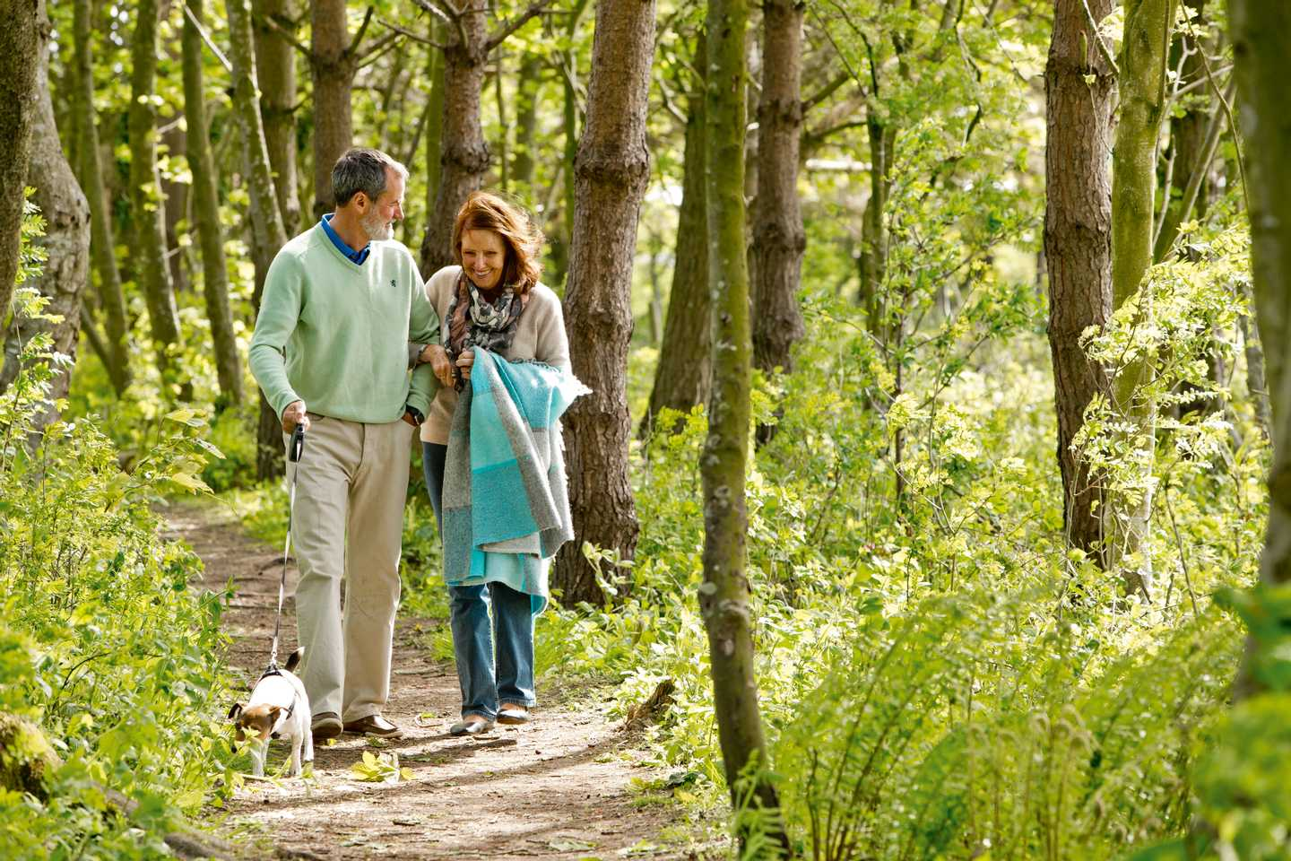 A couple walking their dog on the nature trail