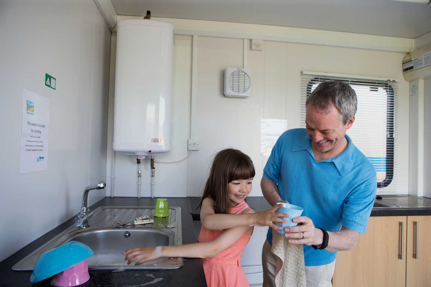 A father and daughter washing dishes