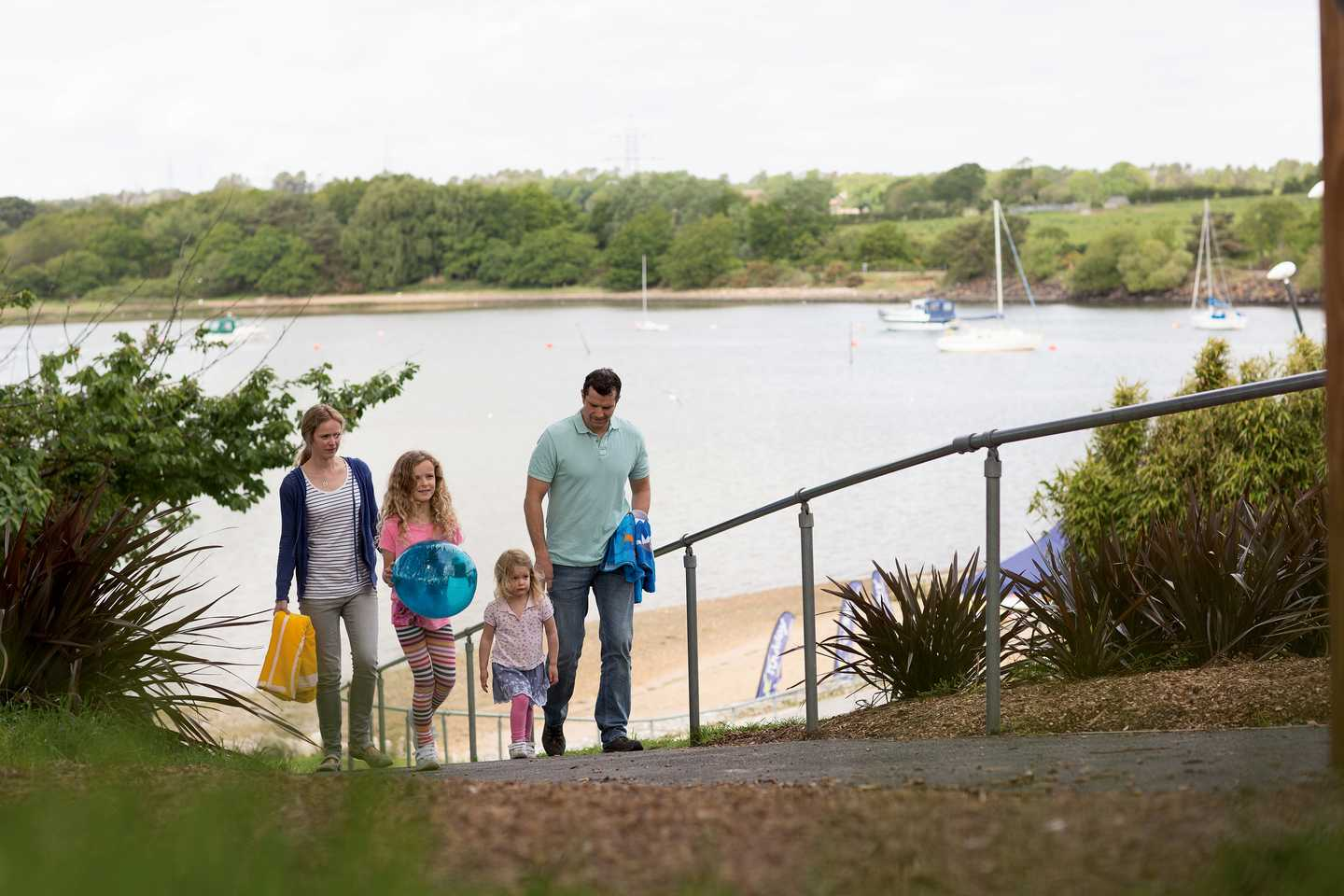 A family walking up a steep path from the marina to the park carrying a fishing net