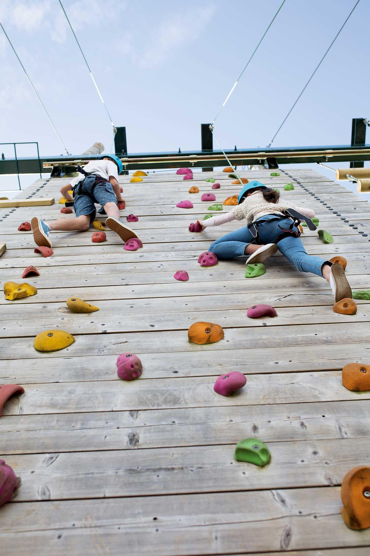 Kids half way up climbing wall