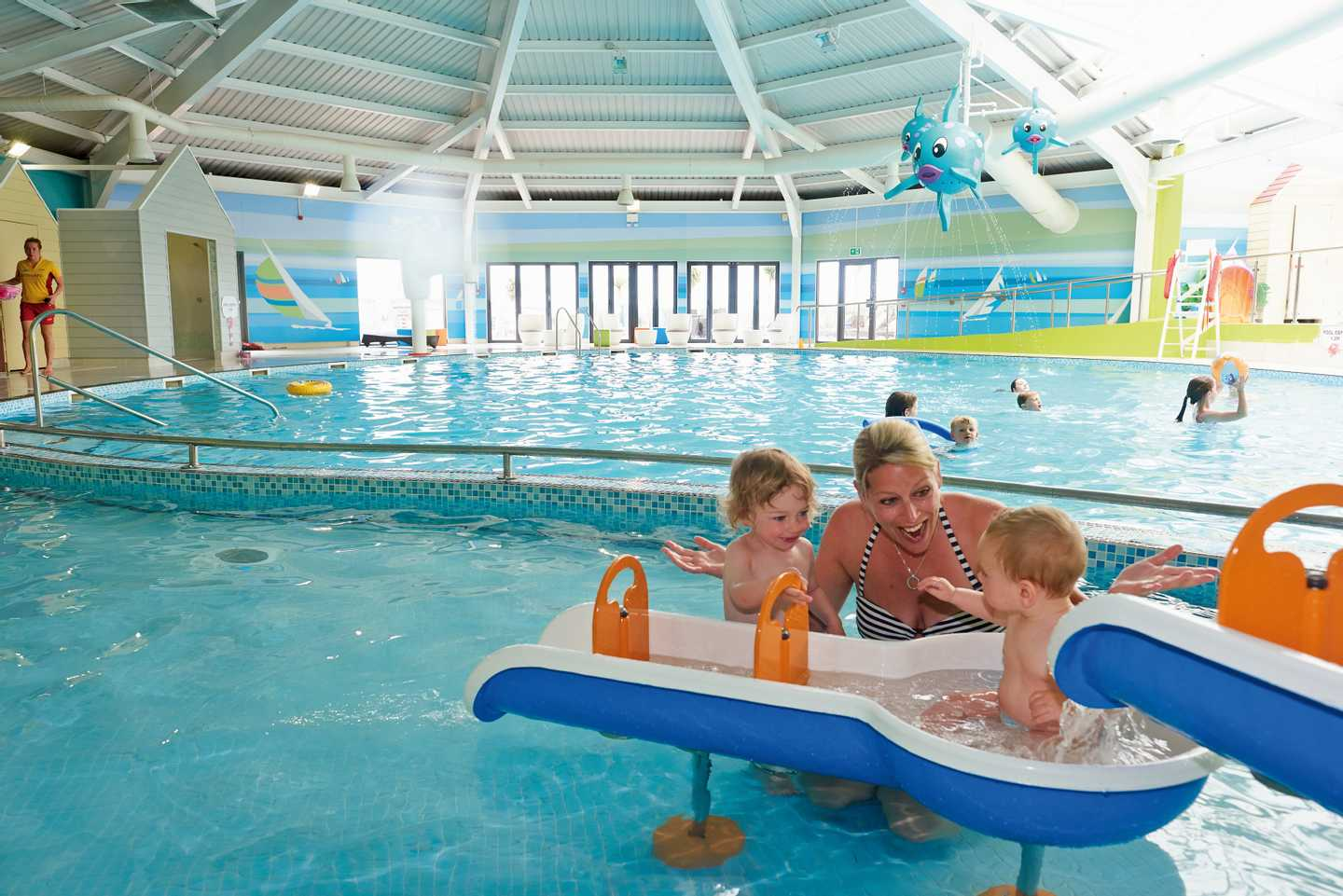 A mum playing with the mini splash area with her two children in the indoor heated swimming pool at Littlesea Holiday Park