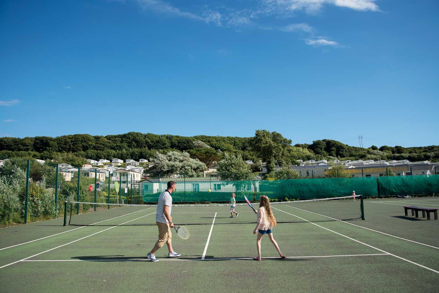 A family playing tennis on the tennis courts